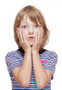 Boy with Blond Hair Suprised, Hands on his Cheeks Royalty Free Stock Photo