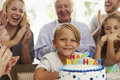 Boy Blows Out Birthday Cake Candles At Family Party Royalty Free Stock Photo