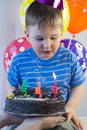 Boy blows out the candles on birthday cake Royalty Free Stock Photography