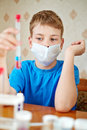 Boy blue t shirt sits table chemical reagents looks test tube which holds his hand Stock Photos