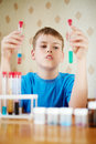 Boy blue t shirt sits table chemical reagents looks two test tubes which holds his hands Stock Image