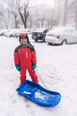 Boy with bob sledge in city heavy snowfall Royalty Free Stock Photography