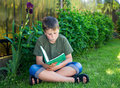 Boy with a book on the grass Royalty Free Stock Photo