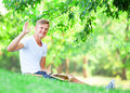Boy with books teen sitting on green grass in the park Stock Photo