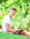 Boy with books teen sitting on green grass in the park Stock Image