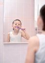 Boy brushing his teeth in front of mirror little the bathroom Stock Photos