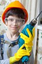 Boy builder in goggles and with a drill Royalty Free Stock Photo