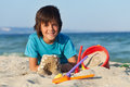Boy building sand castles on the sea shore decorating them with shells Stock Image
