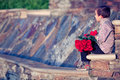 Boy with bunch of red roses waiting small dozen anticipation at a small artificial waterfall Royalty Free Stock Images