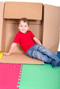 Boy in cardboard box little playing with Royalty Free Stock Image