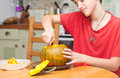 A boy carving halloween pumpkin on a kitchen table candid shot Royalty Free Stock Photography