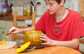 A boy carving halloween pumpkin on a kitchen table candid shot Stock Photos