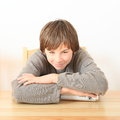Boy with case for money little smiling kid sitting behind wooden table and holding and protecting Stock Photography