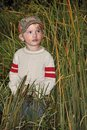 Boy and cattails a standing in along the road Stock Photography