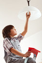 Boy changing lightbulb installing an energy saver resources awareness concept Stock Image