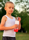 Boy child caucasian drinking juice beverage plastic bottle hot weather summer day outdoor Stock Photography