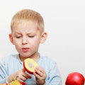 Boy child kid preschooler with knife cutting fruit apple at home blond kitchen childhood Stock Image