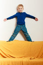 Boy child kid preschooler standing on back rest of sofa interior blond happy playing at home childhood Royalty Free Stock Images