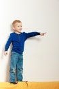 Boy child kid preschooler standing on back rest of sofa interior blond happy and showing blank copyspace playing at home childhood Royalty Free Stock Photos