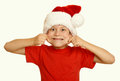 Boy child make faces in santa hat, having fun and emotions, winter holiday concept, yellow toned Royalty Free Stock Photo