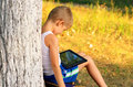 Boy child playing with tablet pc outdoor forest on background computer game dependence concept Stock Photos