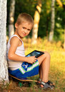 Boy child playing with tablet pc sitting on skateboard outdoor forest background game dependence concept Stock Photo