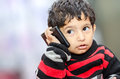 Boy child talking over mobile phone sitting on bed Royalty Free Stock Photos