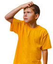 Boy child teen blonde in yellow shirt scratching his head looking up thinking Stock Photography