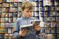 Boy chooses one of two dvd in special store Royalty Free Stock Photos