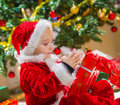 Boy and christmas gift opens a tree gifts on background Royalty Free Stock Image