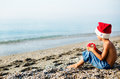 Boy in christmas hat next to the sea sitting on beach Stock Images