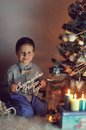 Boy and christmas tree in the snow with lights garlands at home Royalty Free Stock Images