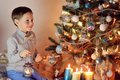 Boy and christmas tree in the snow with lights garlands at home Stock Images