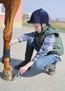 Boy cleans a hoof of horse equestrian sport Royalty Free Stock Photography