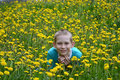 The boy on a clearing from dandelions happy teenager sits Stock Photography