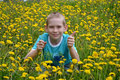 The boy on a clearing from dandelions happy teenager sits Royalty Free Stock Photography