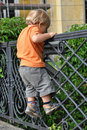 Boy climbing fence Stock Photo