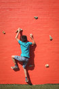 Boy climbing orange wall Royalty Free Stock Photo