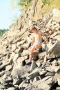 Boy climbing rock hill in grey shorts and crocks steep on big stones Royalty Free Stock Photo