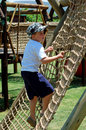 Boy climbing a rope ladder in playground