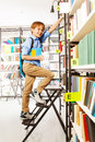 Boy climbing on step ladder in library Royalty Free Stock Photo