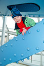 Boy climbs on the bridge climbing a metal structure covered Stock Images