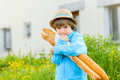 The boy clings to his two breads french baguette Royalty Free Stock Photo