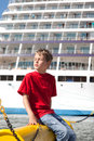 Boy closed eyes, sitting in front of ship Royalty Free Stock Image