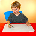 Boy coloring on blank piece of paper a young a while sitting in a chair at a red table Royalty Free Stock Image
