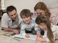 Boy Coloring Pictures While Family Looking At It On Floor Royalty Free Stock Photo