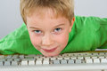 Boy with computer shoring his head on keyboard Royalty Free Stock Images