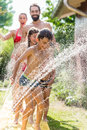 Boy cooling down with garden hose, family in the background Royalty Free Stock Photo