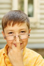 Boy corrects glasses near house Royalty Free Stock Image