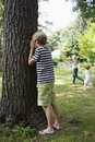 Boy covering eyes in garden standing by tree with covered as children running the background Royalty Free Stock Photos